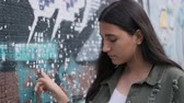 sardas : thoughtful young brunette girl holds her hand on the wall with graffiti and looks into the camera