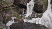 A female tourist climbs a rock and raises his hands up in front of a large waterfall. Happy girl enjoys success