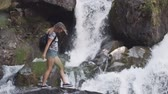 explorador : A female tourist with a backpack climbs onto the edge of a cliff and raises his hands up in front of a large waterfall. Happy girl enjoys success. slow motion Archivo de Video