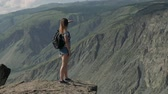 Female traveler stands in front of a cliff of a mountain and looks into the distance