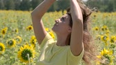 cabelos cacheados : Beautiful young girl posing standing in a field with sunflowers. slow motion Vídeos