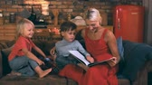 estudio biblico : Beautiful mother reads a book to two sons sitting on a sofa against the background of the kitchen and smiling boy with blond hair laughs, cheerful and happy family spends the evening together