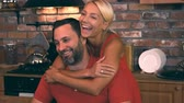 compleanno : Beautiful blonde hugs her husband in the kitchen and smiles