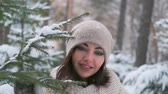happy new year : portrait of a beautiful young girl in a winter park near the Christmas tree. slow motion
