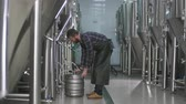 A male brewer with a beard connects a keg to a beer tank and fills it with beer. Stockvideo