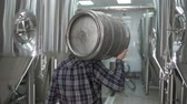 A working male brewer carries a keg filled with beer as he passes beer tanks. close-up. back view