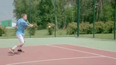 habilidade : Tennis player uses backhand slice on the half court. Slow motion