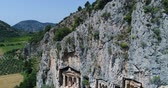 著しい : Aerial. Ancient Lycian rock-cut tombs, Fethiye, Turkey. Camera moves down. 4K.