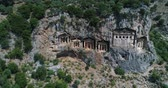 artefato : Aerial. Ancient Lycian rock-cut tombs, Fethiye, Turkey. Camera moves down. 4K.