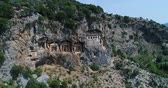реликвия : Aerial. Ancient Lycian rock-cut tombs, Fethiye, Turkey. Camera moves down. 4K.