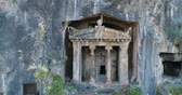 artefato : Aerial. Ancient Lycian rock-cut tombs, Fethiye, Turkey. Camera moves up, 4K.