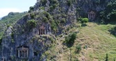 jaskinia : Aerial. Ancient Lycian rock-cut tombs, Fethiye, Turkey. Camera moves up, 4K.