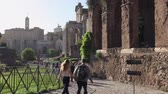 Rome, Italy - May 7, 2017: Archaeological area of ??Palatine, tourists walk on the ancient sacred street of the Roman Forum. On the right, ancient porch and in the distance the columns of the Temple of Antoninus and Faustina.