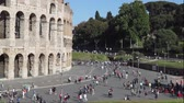 Colosseum Square, a crowd of tourists and citizens walk through the pedestrian area in front of the monument.