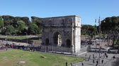 Arch of Constantine, a crowd of tourists and citizens walk in the pedestrian area in front of the ancient monument. Stok Video