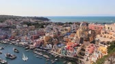 Procida, Corricella marina at sunset. Panoramic view of the old village of fishermens houses and the marina of Corricella, a classic panoramic view of the island of Procida, Italy.