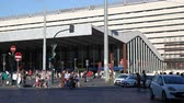 Rome, Italy - June 4, 2016: main facade of the Termini Station, travelers entering and leaving, pedestrian crossing, traffic lights stop drivers.