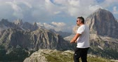to take : Using his cell phone. In the background the dolomite rocks of the Italian alpine mountains. Stock Footage