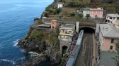 Riomaggiore (SP), Italy - September 16, 2017: Train station seen from above. With the descent of the passengers and the ascent, before the restart. In the background the rocky coast stands out against the blue sea of ??this tourist resort.