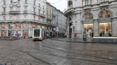 Milan, Italy - October 27, 2018: city tram line, passing of public service trams at a crossroads in the center of the city. Daytime film of a rainy autumn day.
