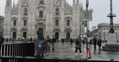 Milan, Italy - October 27, 2018: at the Piazza Duomo underground exit, pigeons in the foreground and in the background of the famous cathedral. Daytime film of a rainy autumn day.