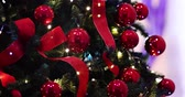 karácsony : Christmas lights - slow focus on decoration, lights, ribbons and red Christmas tree baubles.