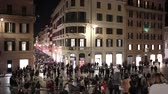 Crowd in Piazza di Spagna, night shots with many people. At the center of the famous Barcaccia fountain, in the background Via Condotti. Time-lapse