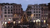 Rome, Italy - February 10, 2019: Crowd in Piazza di Spagna, night shots with many people. At the center of the famous Barcaccia fountain, in the background Via Condotti.