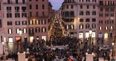 квадраты : Rome, Italy - February 10, 2019: Crowd in Piazza di Spagna, night shots with many people. At the center of the famous Barcaccia fountain, in the background Via Condotti.