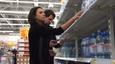 vacuity : Young couple compare two bottles of water among themselves. Stock Footage