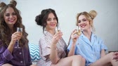 camisola : Happy girlfriends with beautiful make-up and stylish hairstyles are happy with a pajama party in the bedroom. Young women cheerfully clink glasses with glasses of champagne.