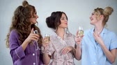 camisola : Young women who are dressed in pajamas are dancing with glasses of champagne in their hands. Happy friends with make-up and stylish hairstyles having a fun on a pajama party in the bedroom.