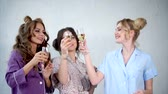 camisola : Young women who are dressed in pajamas are dancing with glasses of champagne in their hands. Happy friends with make-up and stylish hairstyles celebrate a pajama party in the bedroom.