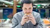alimentação pouco saudável : A young man eats a sandwich, which consists of bread, meat cutlets and vegetables. A man is eating a hamburger at a shopping center food court.