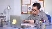 zdůraznit : A busy man, similar to a manager, fills in the reporting documentation for his firm. A person with poor eyesight makes a marking pen on paper, on his desktop is a laptop