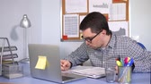 zdůraznit : Manager fills in the reporting documentation for his firm. A person with poor eyesight makes a marking pen on paper, on his desktop is a laptop.