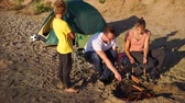 vinha : A young family who came to a sandy beach in order to relax with a tent, fry meat sausages on fire, a child stands next to him and awaits an evening dinner in the open air Vídeos