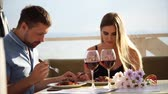 doba jídla : A loving couple of spouses eat dinner in a restaurant during the day, a man and a woman eat the main dishes and drink wine from glasses near the river