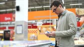 precooked : Young man looking over the packages with precooked food in the section with frozen products Stock Footage
