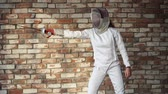 meç : Swordsman is showing some simple moves with a fencing sword. She is standing in a costume against brick wall.