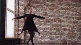 against window : Ballerina is dancing in a training hall.She is whirling and falling on a floor then rising Stock Footage