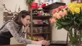 compor : a young and pretty woman works as a florist in a flower shop, a lady holds a phone in her hand and talks to a client, she writes orders for bouquets to a notebook Vídeos