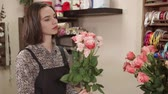 collects : a young and pretty woman makes a bouquet in a flower shop, a lady works as a florist and picks up roses of the right diameter and color to compose a bouquet