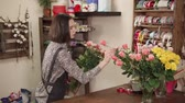 kwiaciarnia : a young woman who looks like a student working as a trainee in a flower shop, a lady leaves a bouquet of pink roses, carefully selects the right flowers Wideo