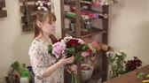 krizantem : a young woman holds a bouquet of chrysanthemums and green leaves in her hand, a florist collects a flower arrangement in a flower stall, this is her small business