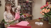wazon : Female florist making a bouquet of different flowers indoor. She is decorating it with ribbons and wraps. Wideo