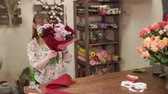 krizantem : a young woman holds in her hand a bouquet of chrysanthemums and green leaves, the florist applies pieces of paper to decorate a natural bouquet Stok Video