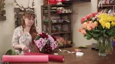 krizantem : a young woman gathered a bouquet in her flower shop, a florist cuts off a ribbon from a beautiful floral composition decorated with red paper