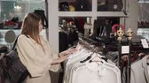 garment : Young woman is considering garment on hangers on shop. Shopping in trendy luxury store Stock Footage