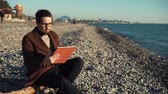aplicativo : a young and handsome man dressed warmly, he sits on a stone beach and holds a tablet in his hands, people work right near the sea, a man enjoys the sea view